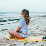 Woman listening on a surfboard