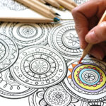 hands working on an adult coloring book page