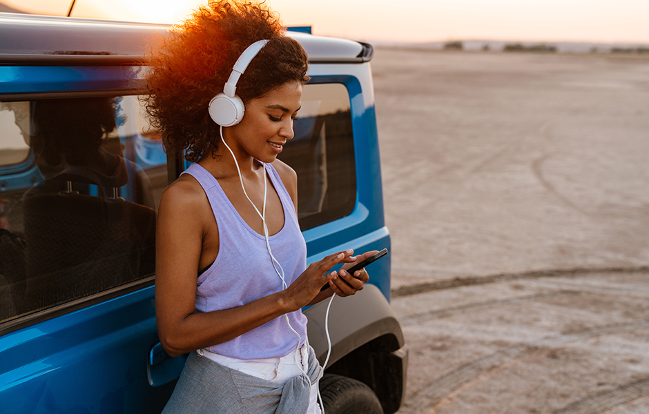 woman leaning against a car with headphones and a device