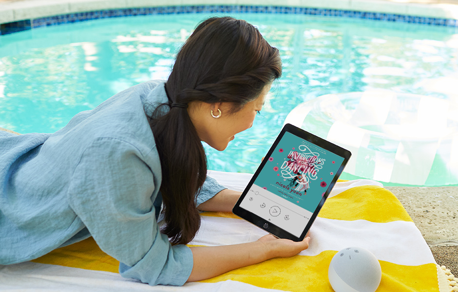 woman laying by a pool holding a tablet device displaying Instructions for Dancing by Nicola Yoon