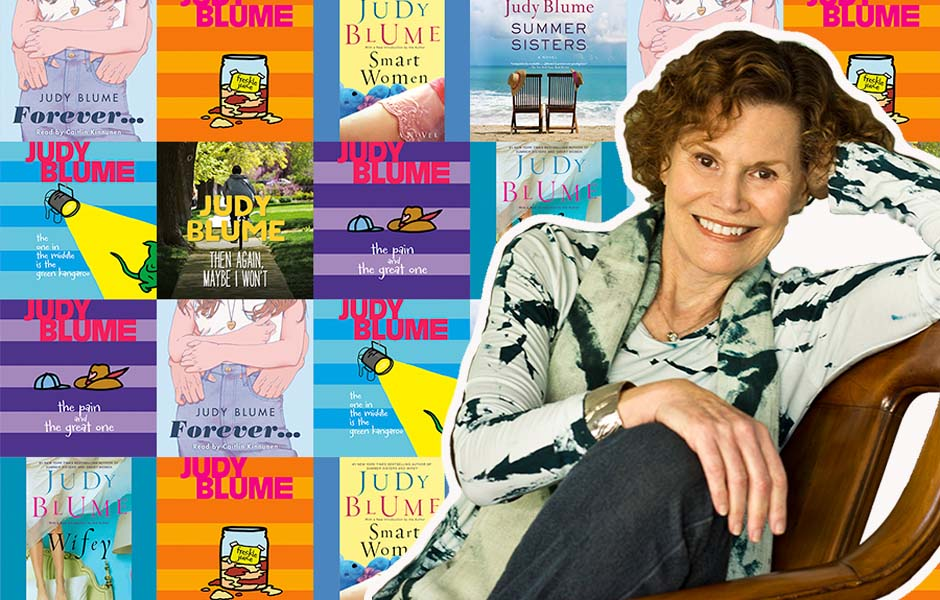 Photo of Judy Blume in front of her books: FOREVER, WIFEY, SUMMER SISTERS, SMART WOMEN, THEN AGAIN MAYBE I WON'T, THE PAIN AND THE GREAT ONE, THE ONE IN THE MIDDLE IS THE GREEN KANGAROO, FRECKLE JUICE